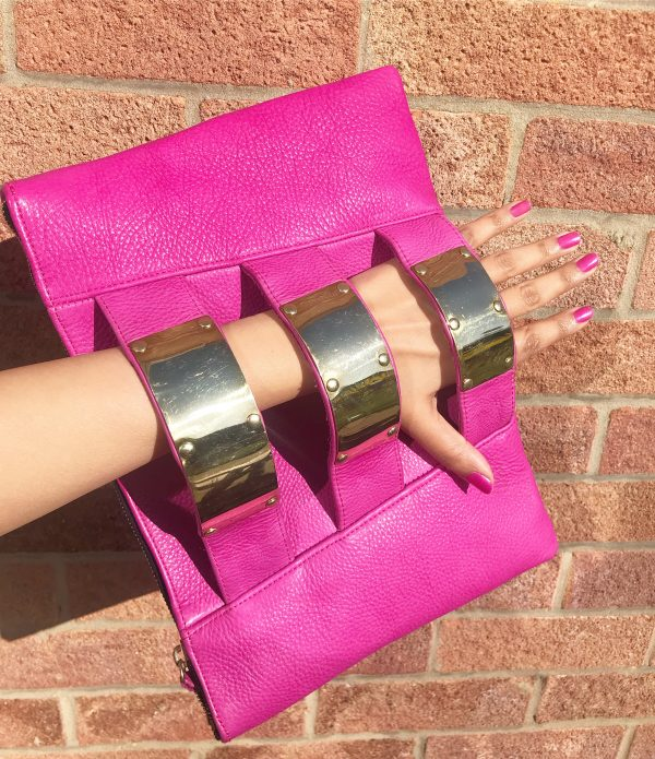 Horizontal rectangle shaped pink clutch bag with 3 armlet strap down the centre decreasing in size. Each strap has a shiny brass cuff attached to it. Image is is showing an arm holding the bag in the armlet straps against a red brick wall.