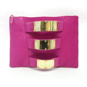 Horizontal rectangle shaped pink clutch bag with 3 armlet strap down the centre decreasing in size. Each strap has a shiny brass cuff attached to it.