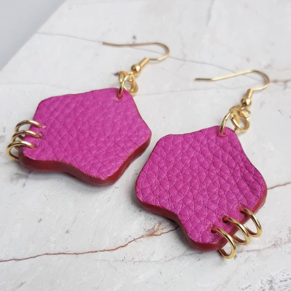 Gold plated hook earrings with an organic shaped offcut piece of leather dropping down. The bottom outer corner of each earring is pierced with three small gold plated rings. Image show the side view of the earrings on a marble slab.