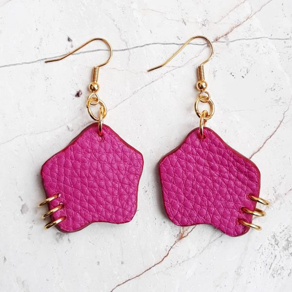Gold plated hook earrings with an organic shaped offcut piece of leather dropping down. The bottom outer corner of each earring is pierced with three small gold plated rings.
