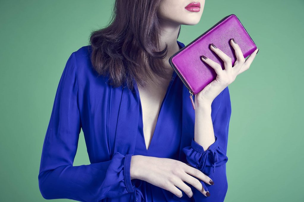 Female model with brown hair holding a pink leather rectangle purse/wallet clutch with gold zip around the outer edges. The model has matching pink lipstick and wearing a v-neck royal blue dress with long sleeves.