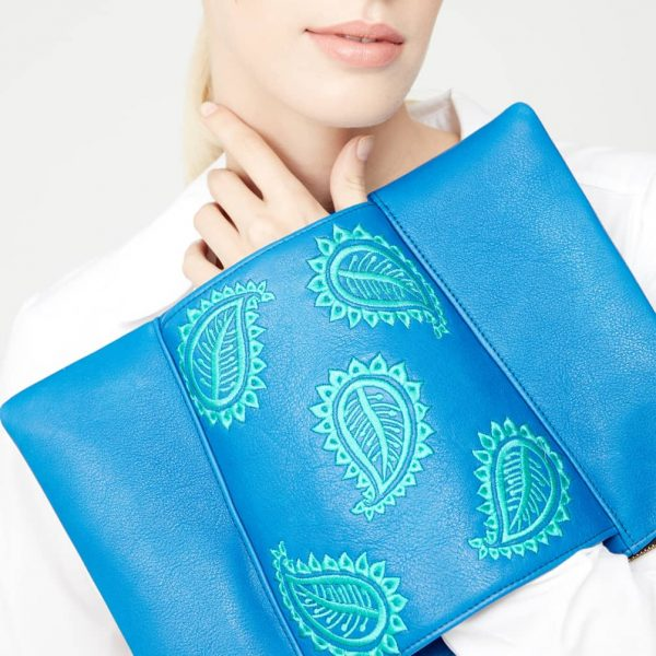 Model holding our classic blue pouch style leather clutch bag with jade green paisley leaf embroidery on centre sleeve detail