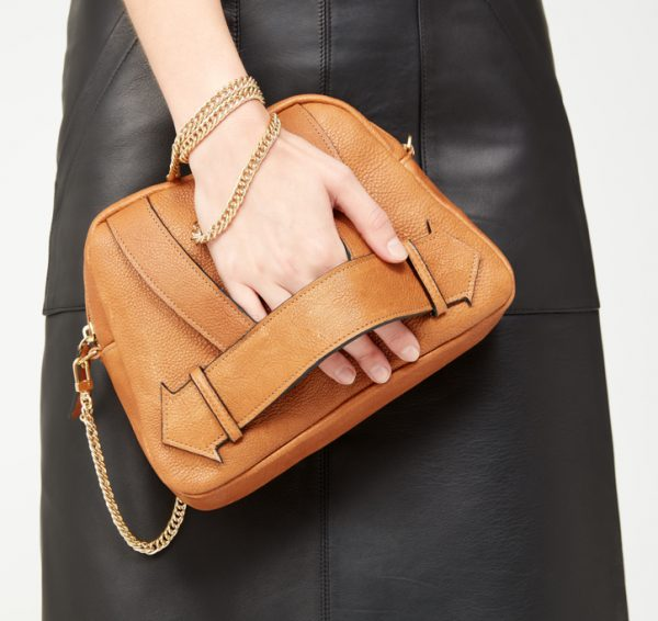 tan leather cross body bag with gold chain strap and clutch strap across the front