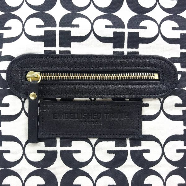 Inside zip pocket detail on black and white monogram print lining with Embellished Truth London embossed in black leather underneath