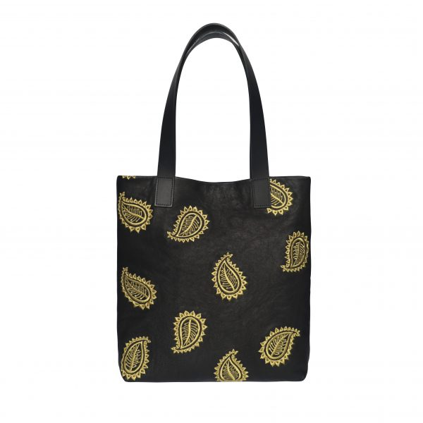 Black leather tote bag with two shoulder strap handles and gold paisley leaf embroidery design in a random pattern on the front.