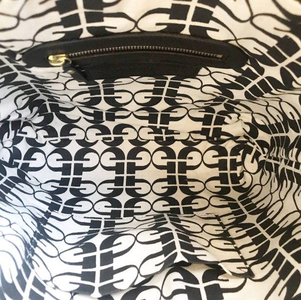 Inside view of leather tote bag with black screenprinted monogram design on off white organic khadi cotton. Shows two pockets, one with a gold zip and on the oppposite side, a patch pocket.