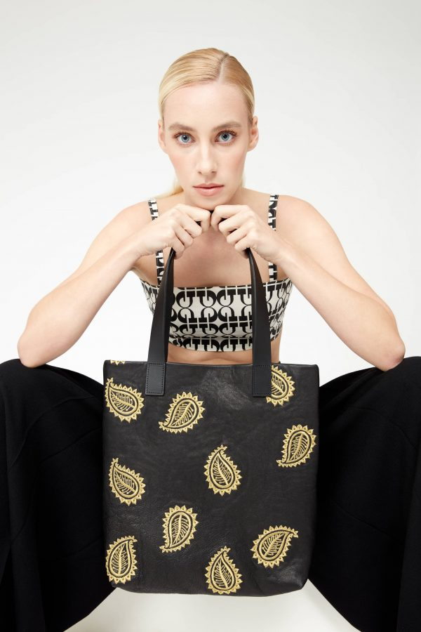 Female model holding a black leather tote bag by the handles with both hands and resting her chin on her hands. The bag is embellished with gold paisley embroidery in a random pattern.