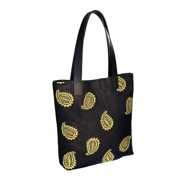 Side view of black leather tote bag with two shoulder strap handles and gold paisley leaf embroidery design in a random pattern on the front.